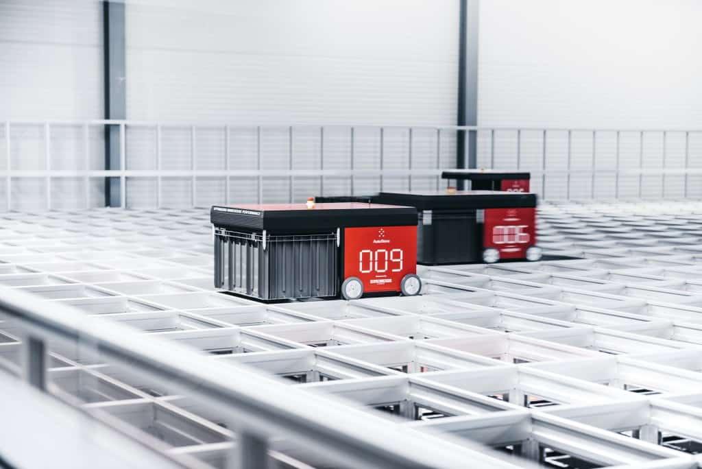 Red AutoStore R5-robotter, der arbejder på et lager.