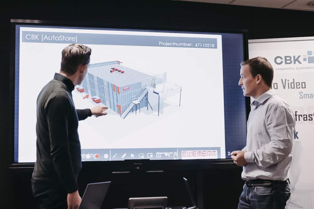 To mænd peger og ser på en tegning af en AutoStore-løsning.