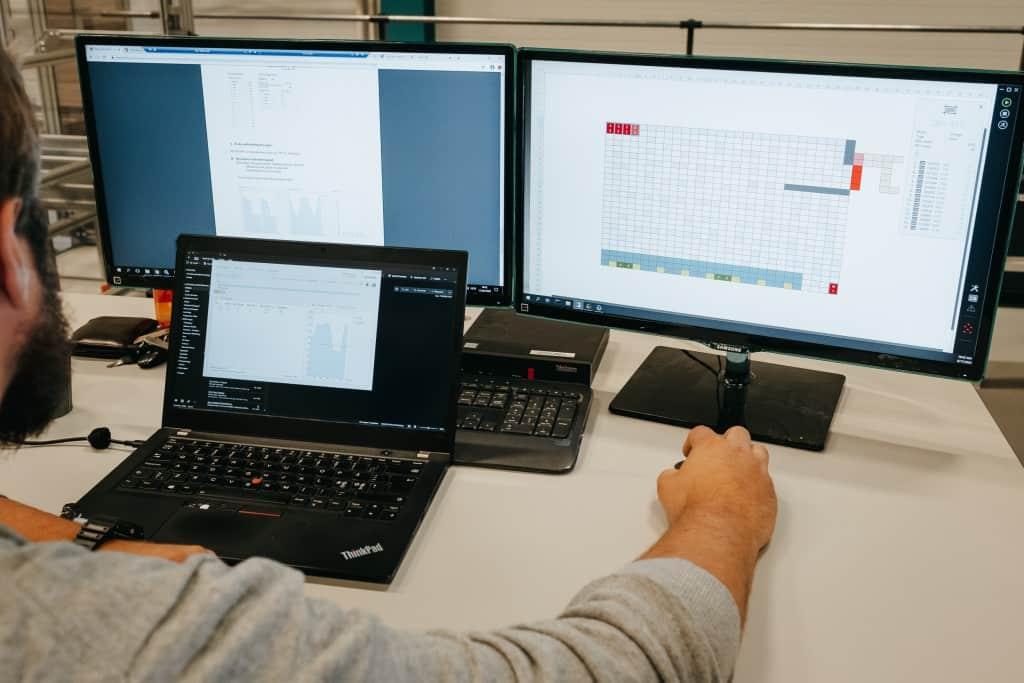 En mand arbejder på AutoStore-løsningen med tre computerskærme.