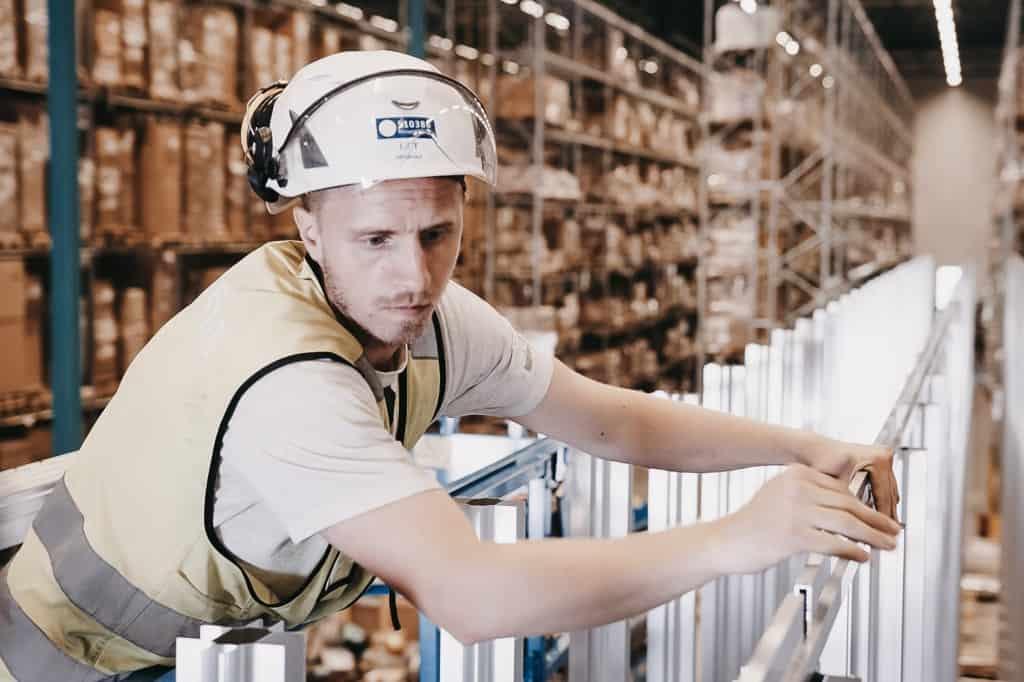En mand med hjelm og gul vest opfører AutoStore-gitteret bestående af aluminiumsøjler.