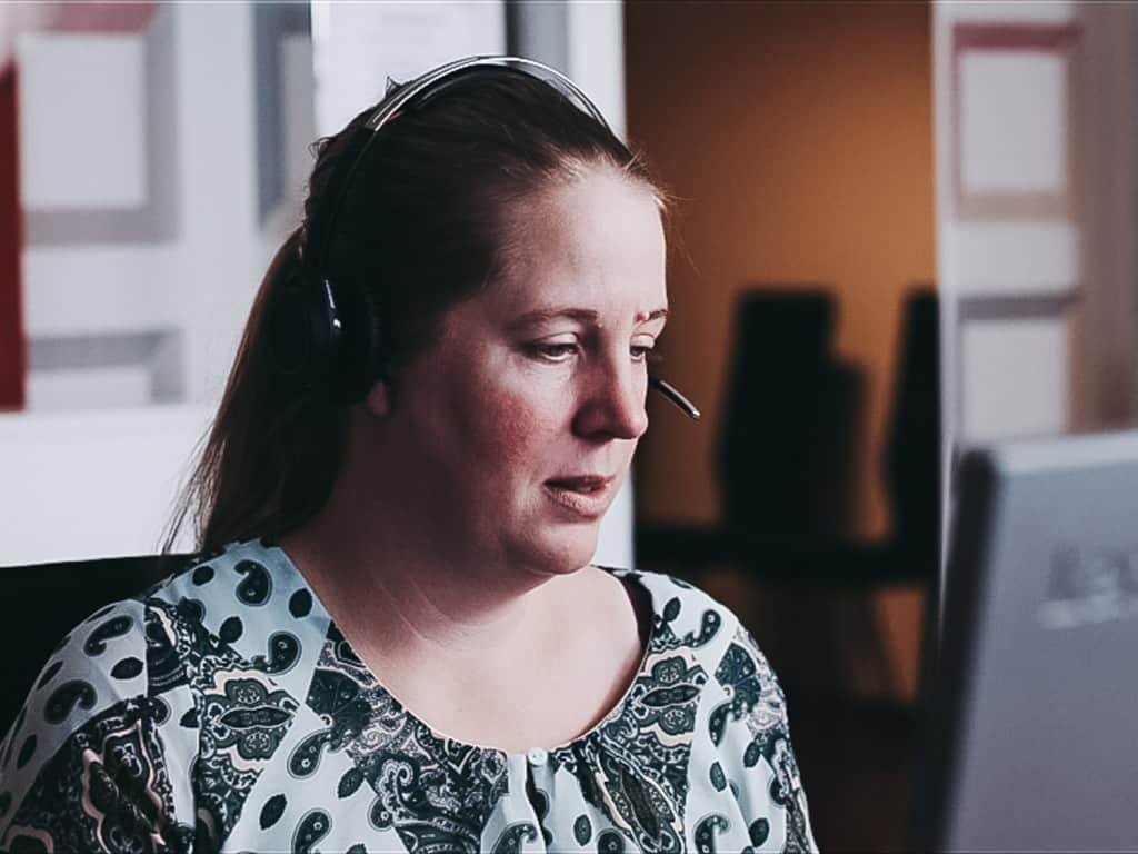 Et nærbillede af en kvinde, som taler i hovedtelefoner foran en computer.