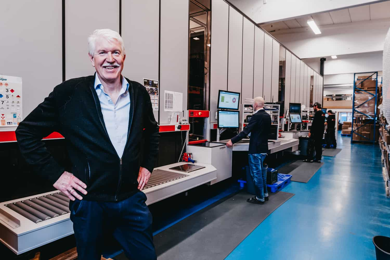 Administrerende direktør, Jan Kleven, smiler stolt til kameraet foran Elotecs AutoStore-løsning med medarbejdere, der betjener portene i baggrunden.