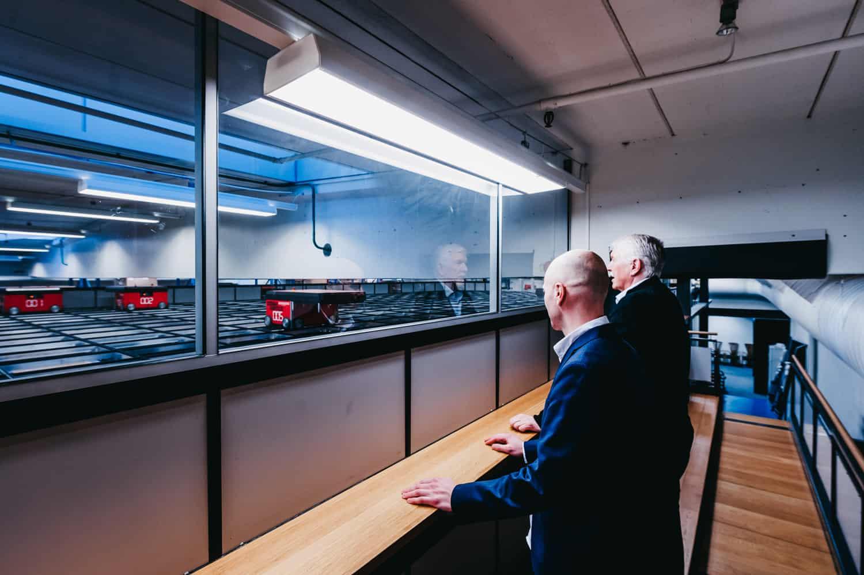 Jan Kleven og Roger Furnes kigger ud mod AutoStore-robotterne på gitteret.
