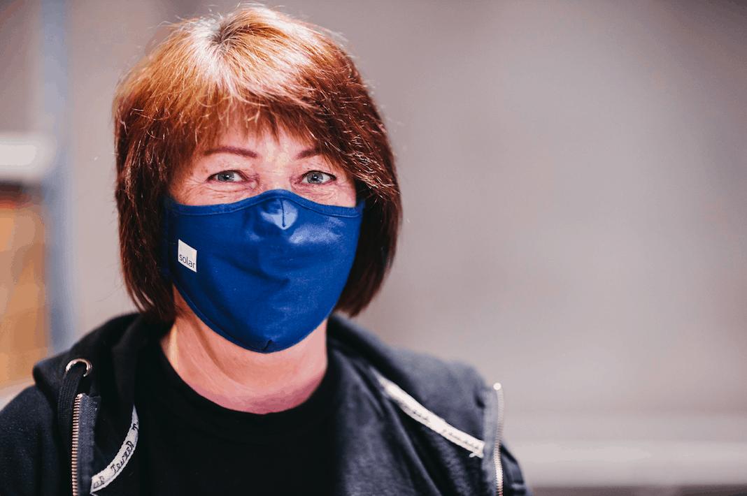 Kvindelig lagerarbejder med mundbind.